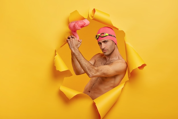 Cara sério e autoconfiante com cerdas segura um flamingo rosa inflado, usa touca de banho e óculos de proteção na testa