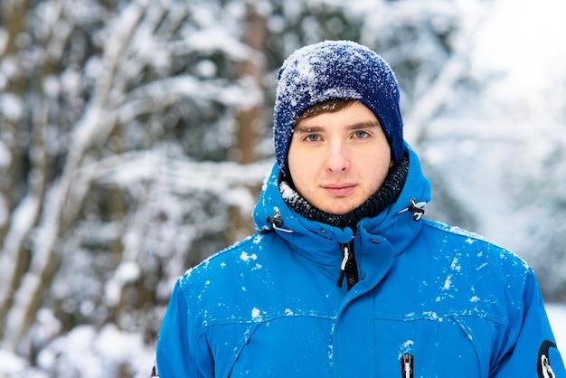 Cara sério, jovem pensativo no fundo de uma floresta de inverno na neve.