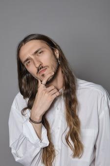 Cara sério pensativo jovem hippie de cabelos compridos, vestindo camisa branca elegante, tocando a barba, tendo um olhar pensativo, profundo em pensamentos, os olhos cheios de dúvida e incerteza. expressão facial humana