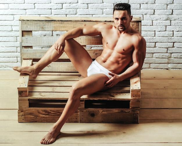 Cara sexy com músculo nu, torso, corpo fechado e cueca de seis blocos em um sofá de palete de madeira na parede de tijolos brancos
