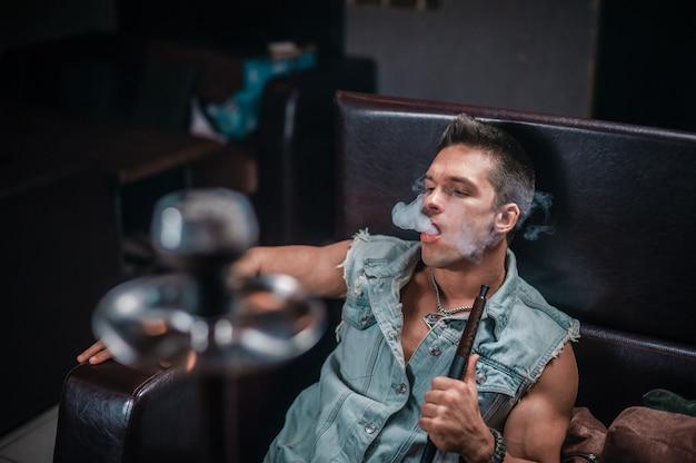 Cara sexy fumando shisha no bar do narguilé