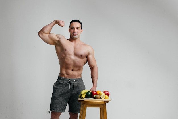 Cara sexy vegan com um torso nu, posando no estúdio ao lado de frutas. dieta. dieta saudável