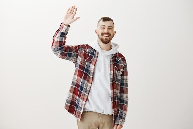 Cara simpático feliz e moderno acenando com a mão levantada para dizer olá, cumprimentando você