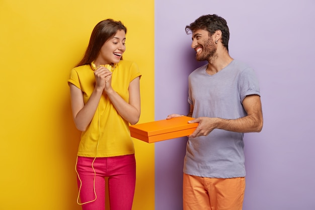 Cara sorridente amigável dá caixa de papelão com surpresa para namorada, parabeniza-a com a vitória. senhora satisfeita em camiseta amarela e calça rosa feliz por receber um pacote de um amigo próximo