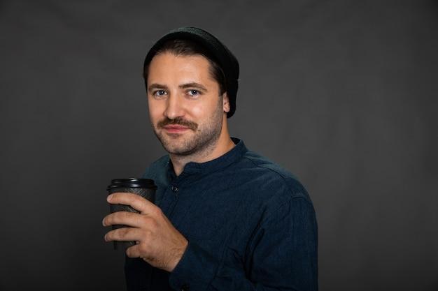 Cara sorridente com a barba por fazer posando com uma xícara de café descartável em um cenário cinza