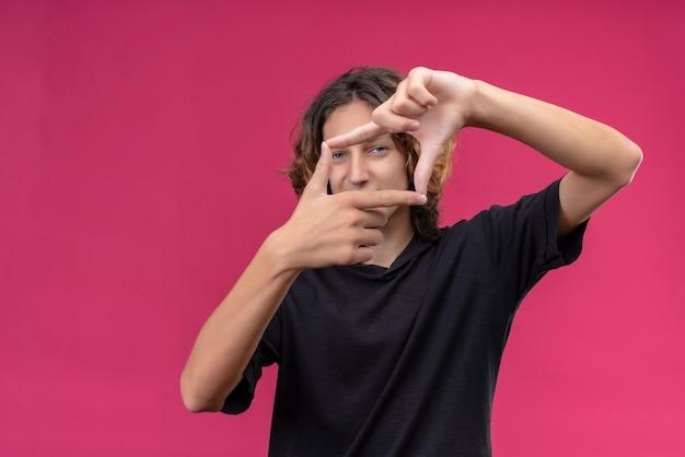 Cara sorridente com cabelo comprido e camiseta preta tirando uma foto na parede rosa