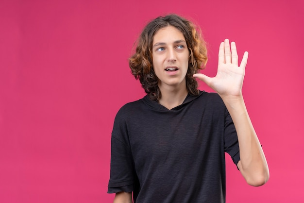 Cara sorridente com cabelo comprido em uma camiseta preta mostrando cinco com os dedos na parede rosa