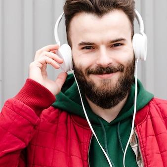 Cara sorridente de close-up com barba e fones de ouvido