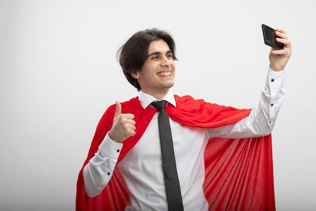 Cara sorridente de jovem super-herói usando gravata tira uma selfie mostrando o polegar isolado no fundo branco