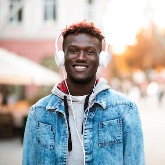 Cara sorridente de vista frontal com fones de ouvido brancos