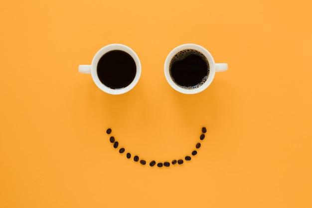 Cara sorridente de xícaras de café e feijão