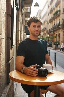 Cara sorridente, descansando à mesa em um café ao ar livre com uma xícara de café e câmera
