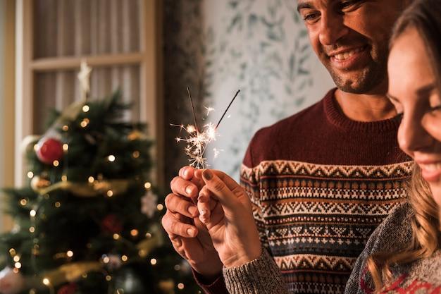 Cara sorridente e alegre mulher com luzes de bengala em chamas perto de árvore de natal