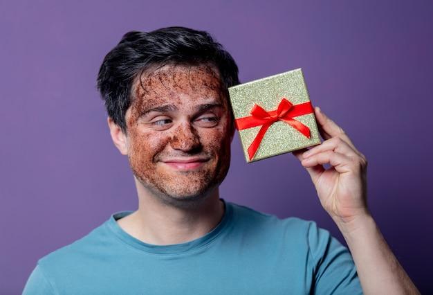 Cara sorridente em uma máscara de cuidados faciais e com caixa de presente