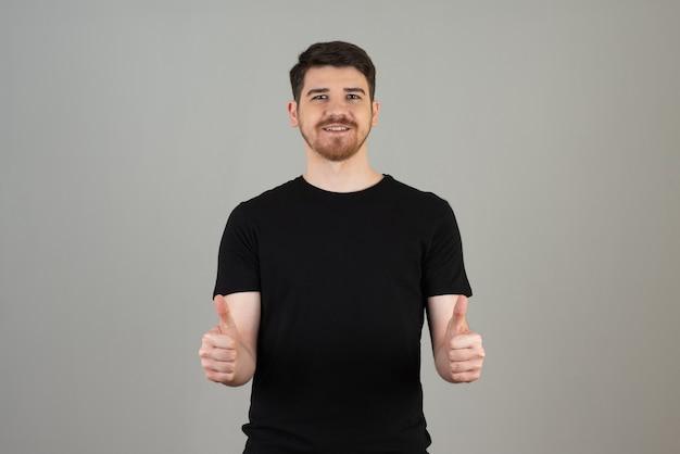 Cara sorridente gesticulando com o polegar em um cinza. Foto gratuita