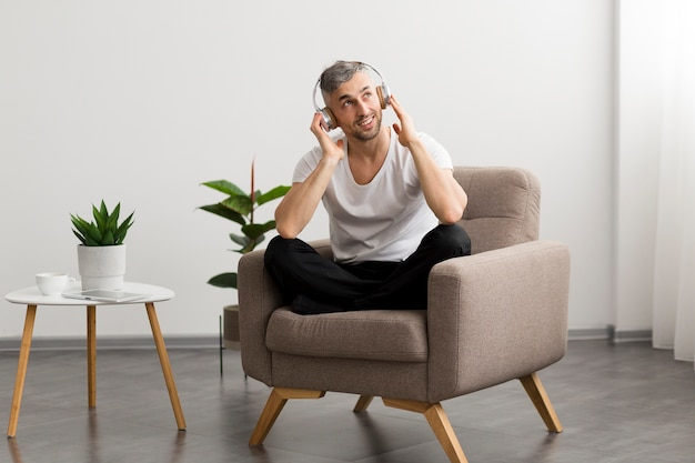 Cara sorridente, sentado em uma cadeira e ouvir música