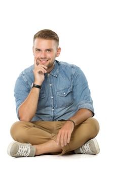 Cara sorridente, sentado no chão, isolado sobre o branco