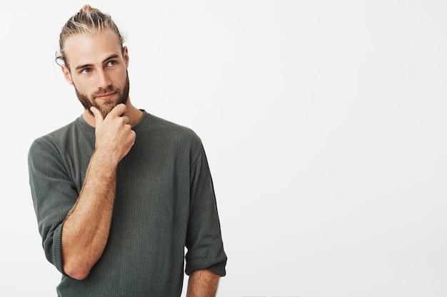 Cara sueco atraente, com cabelos elegantes e barba na camisa cinza, segurando o queixo e olhando pensativamente, pensando de lado