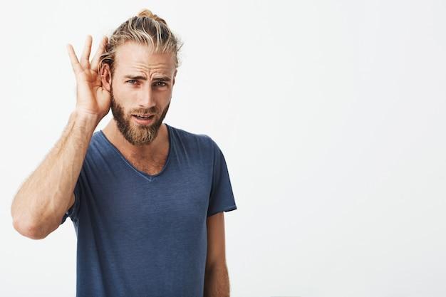Cara sueco bonito com barba e penteado legal, segurando a mão perto da orelha