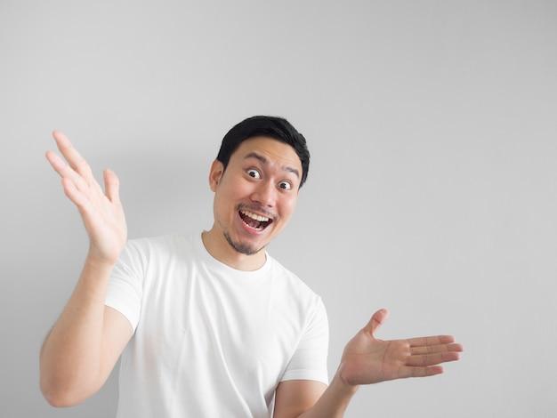 Cara surpreendida do homem asiático feliz na luz branca da camisa - fundo cinzento.
