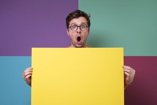 Cara surpreso e animado de óculos segurando um espaço de cópia amarela