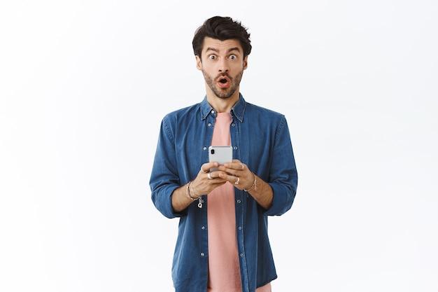 Cara surpreso e atônito recebe novo smartphone, dobrando os lábios em uau e olhando para a câmera animada e chocada, veja algo incrível online, peça agora, parede branca
