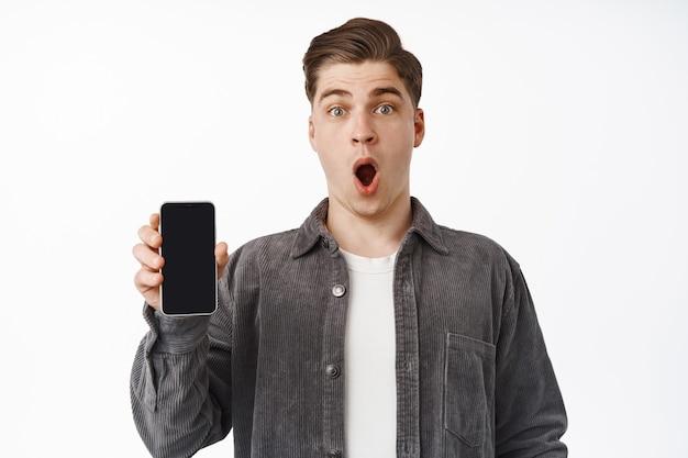 Cara, suspiro de admiração, parece surpreso com o aplicativo incrível, mostra a tela do smartphone, aplicativo de interface, vestindo roupas casuais em branco