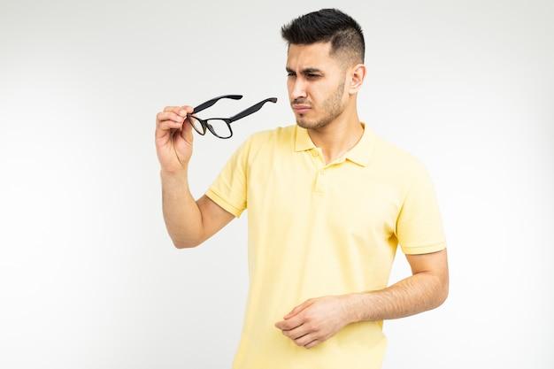 Cara tem olhos secos, tirando os óculos em um fundo branco