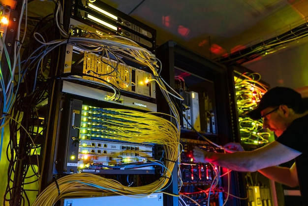 Cara tentando hackear servidores na sala de cabos