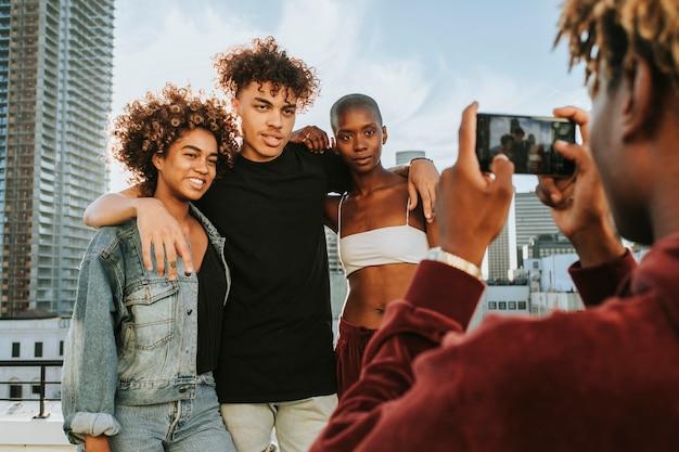 Cara tirando uma foto de seus amigos em um telhado