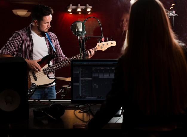 Cara tocando guitarra e mulher gravando por trás vista