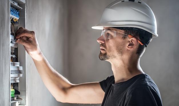 Cara, um eletricista trabalhando em uma central telefônica com fusíveis. instalação e conexão de equipamentos elétricos.