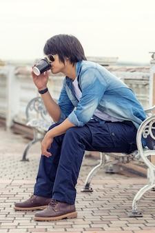 Cara vestindo calças cargo e beber um café