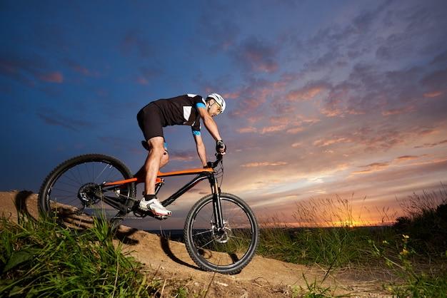 Cara vestindo capacete e sportswear em bicicleta de montanha, descendo a colina ao pôr do sol