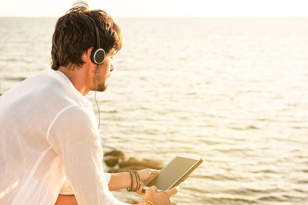 Cara visto de trás ouvindo música com fones de ouvido em um tablet em um destino de férias