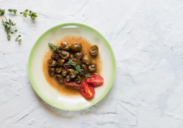 Caracóis apulianos deliciosos chamados munaceddi com molho de tomate, orégano em uma mesa de luz