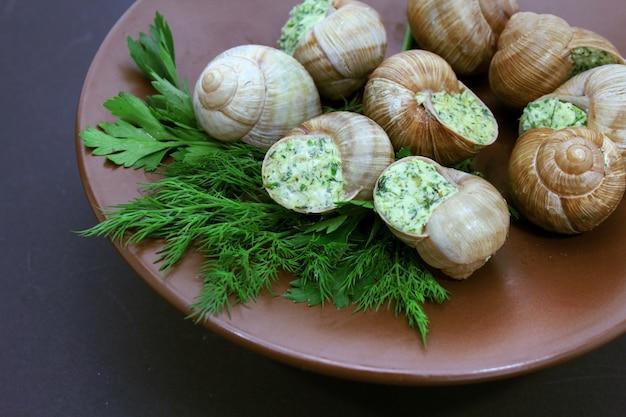 Caracóis de escargot cozidos com manteiga de alho no prato
