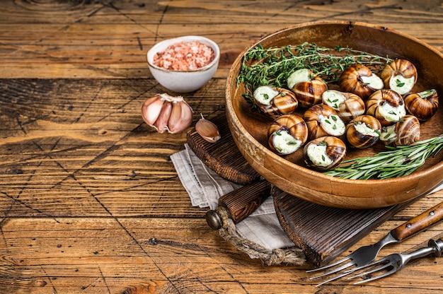 Caracóis escargot francês com manteiga de alho em uma placa de madeira. fundo de madeira. vista do topo. copie o espaço.