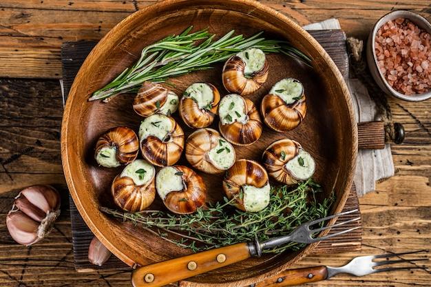 Caracóis escargot francês com manteiga de alho em uma placa de madeira. fundo de madeira. vista do topo.