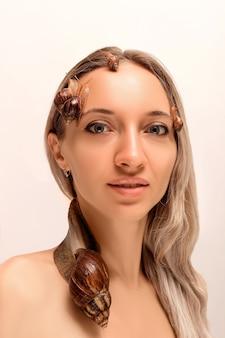 Caracóis rastejando no rosto de uma jovem loira linda