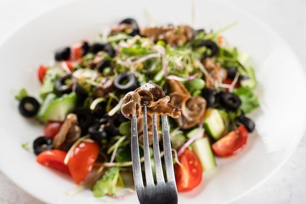 Caracol de uva escargot no garfo perto de salada verde em fundo branco. cozinha gourmet francesa.