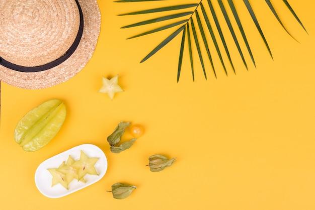 Carambola de frutas, acessórios de praia e folhagem de planta tropical em papel colorido. fundo de verão com estrelas do mar e frutas