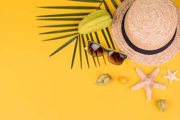 Carambola de frutas, acessórios de praia e folhagem de planta tropical em papel colorido. fundo de verão com estrelas do mar e frutas Foto Premium