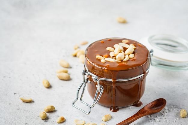 Caramelo salgado caseiro com as porcas no frasco de vidro, espaço da cópia. ingrediente para snickers de bolo.