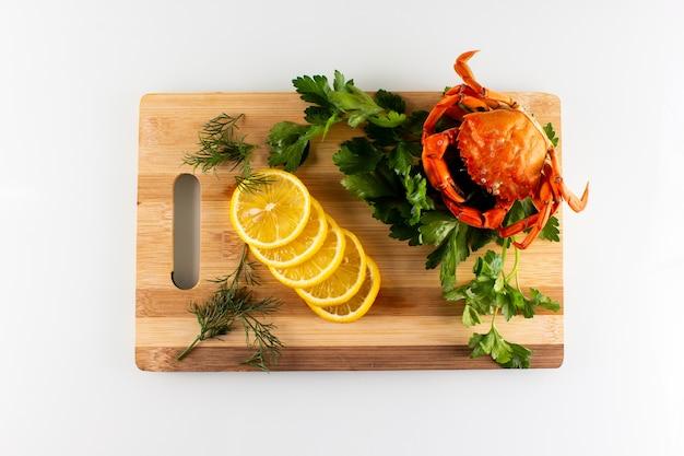 Caranguejo com limão e salsa em uma tábua de cortar