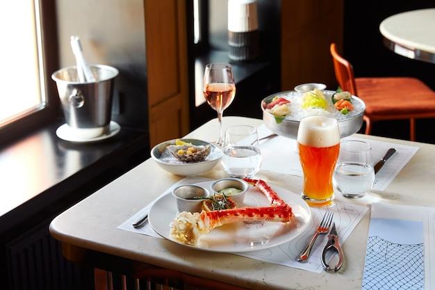 Caranguejo cozido de frutos do mar com molhos de cerveja na mesa do restaurante