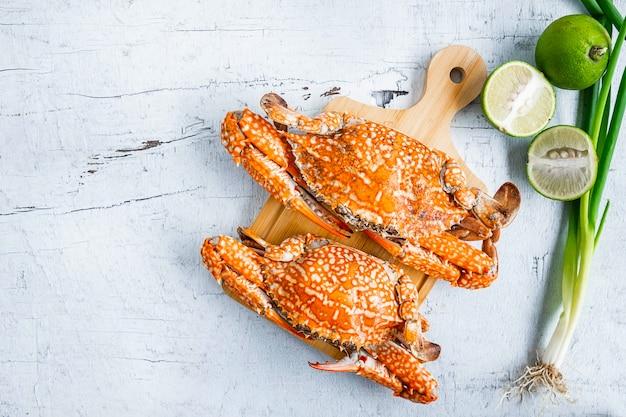 Caranguejo cozido no vapor de frutos do mar em um fundo branco de madeira