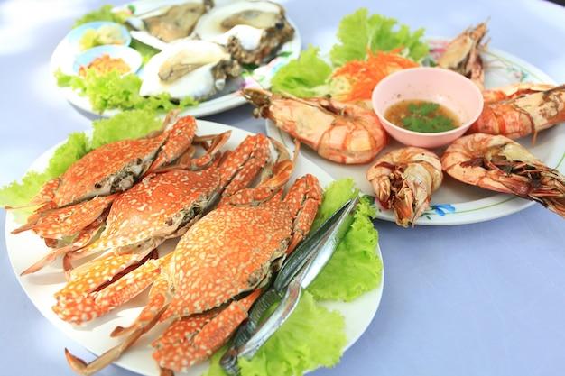 Caranguejo cozido no vapor, ostras frescas e camarão grelhado, colocado em um prato