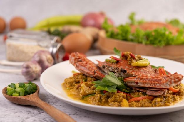 Caranguejo em pó curry frito em um prato branco no chão de cimento.