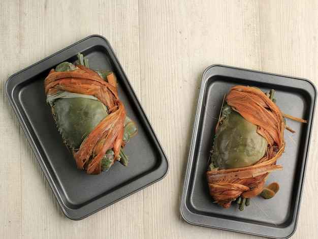 Caranguejo fresco e cru amarrado na bandeja, pronto para cozinhar